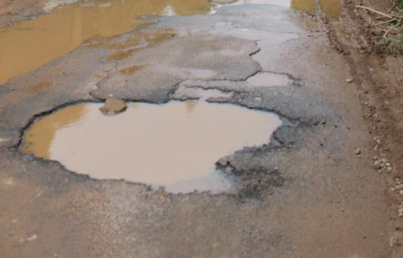Trou béant et plein d'eau dans une route de fort vayron